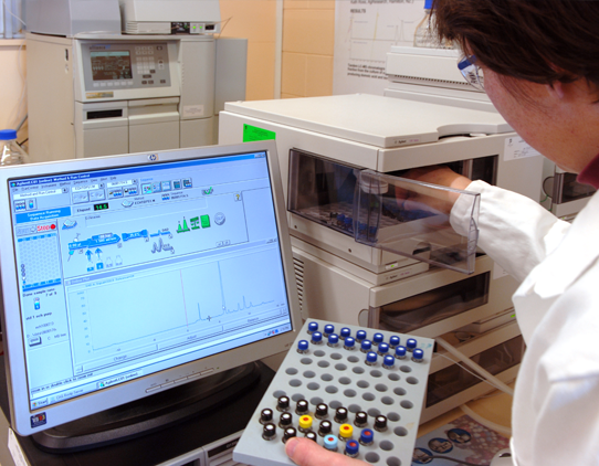 A scientist wearing a labcoat places vials into an instrument. A computer monitor is in the foreground.