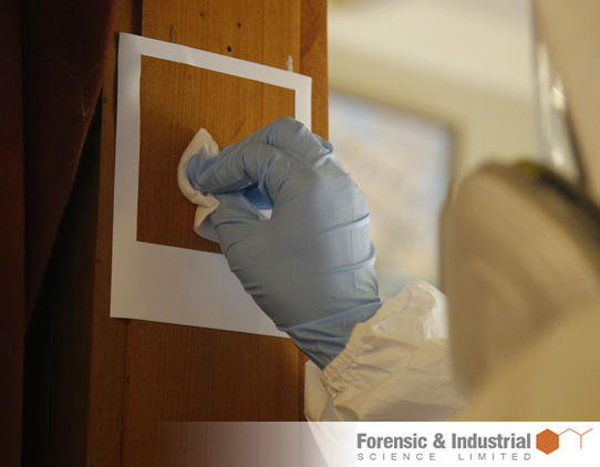 A close up photograph of a technician taking a swab sample of an area of timber. The technician is wearing full protective gear.