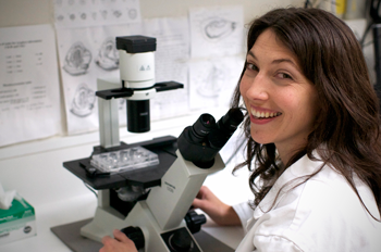 A scientist wearing a white labcoat is working at a microscope.